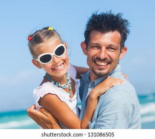 Closeup portrait of father with daughter having fun on tropical beach