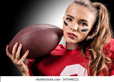 Close-up portrait of female american football player holding ball and looking at camera isolated on black