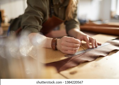 Closeup portrait of female artisan working with leather in workshop, copy space