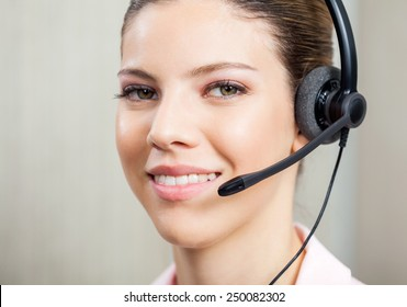 Closeup portrait of female customer service agent wearing headset in office