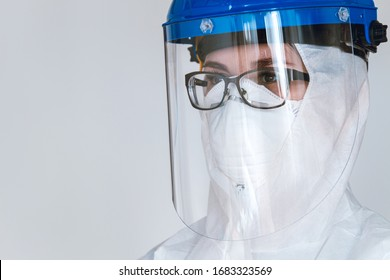 Close-up portrait of female doctor wearing  protective suit to fight coronavirus pandemic covid-2019. Protective googles, respirator.
