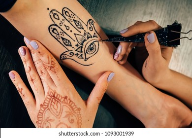 Closeup portrait of female hand being decorated with henna hamsa tattoo.
