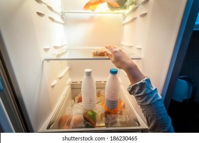 Closeup portrait of female hand taking donut from fridge
