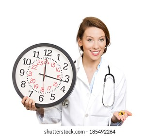 Closeup portrait female health care professional, doctor, nurse with stethoscope holding clock, pills, reminder take medications, isolated white background, clipping path. Patient visit, appointment