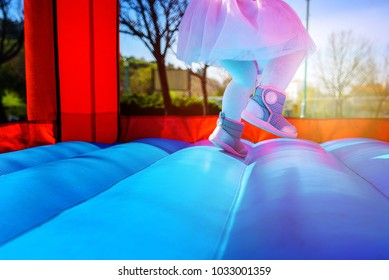 Close-up portrait of female joyful little girl legs jumps on a big inflatable trampoline outdoors in the park.