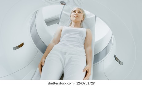 Close-up Portrait of a Female Patient Lying on a CT or MRI Scan, Bed is Moving inside Machine Scanning Her Body and Brain. In Medical Laboratory with High-Tech Equipment.