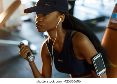 Close-up portrait of fitness instructor african american woman working out with dumbbells at the gym and listens music in earphones