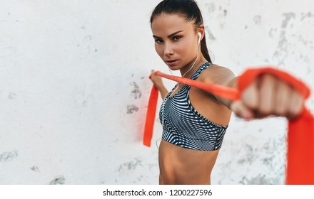 Closeup portrait of fitness woman standing against concrete wall doing stretching exercises holding a red resistance band. Athletic female listen the music on earphones during workout outdoor.
