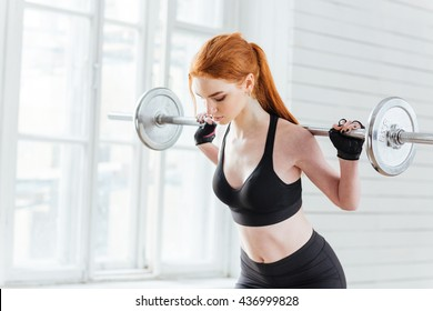 Close-up portrait of a fitness young girl doing squats with barbell at the gym