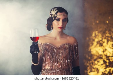 Closeup portrait flapper woman with glass wine. holiday headband finger wave hairstyle, vintage style 20s dress evening makeup red lips smokey cat eyes. Backdrop golden room smoke. Elegant prom image