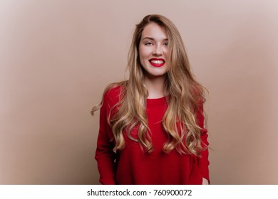 Close-up portrait of friendly charming woman with light-brown hair and red lips wearing red shirt on beige background. Happy girl posing at camera and smiles on isolated background with truly emotions