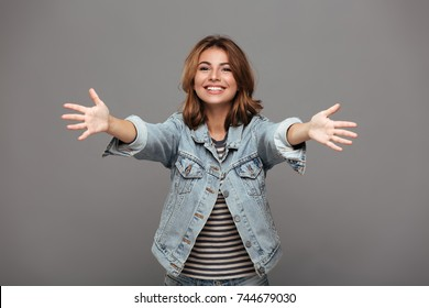 Close-up portrait of friendly pretty woman stretching her arms, wants to hug you, looking at camera, isolated on gray background