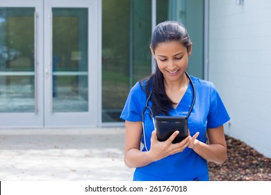 Closeup portrait of friendly, smiling confident female doctor, healthcare professional in blue scrubs with stethoscope, analyzing patient data on black digital tablet, outside hospital background