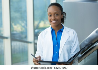 Closeup portrait of friendly, smiling confident female doctor, healthcare professional with labcoat, holding pen to face and holding notebook pad. Isolated hospital clinic background.