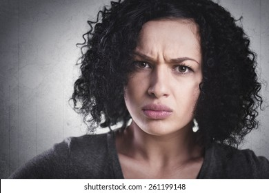 Closeup portrait of a frowning woman, being angry and mad, isolated on grey background.
