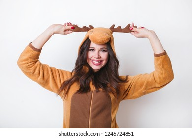 A close-up portrait of funny cute young woman in pajamas looking in kamera on white background