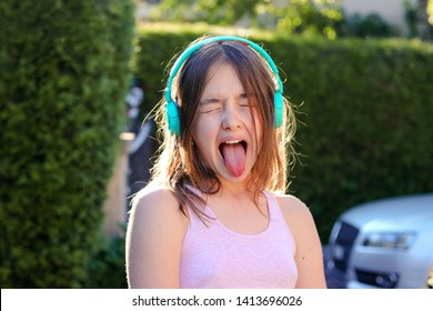 Close-up portrait of funny preteen girl with wireless headphones on head with closed eyes and open mouth with stuck out tounge. Teenager age emotions and protest