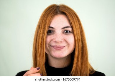 Closeup portrait of a funny redhead teenage girl with childish hairstyle isolated on white backround.