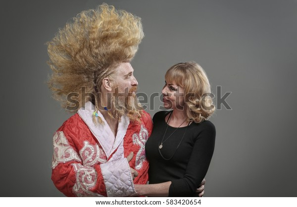 closeup portrait of funny Santa Claus with a mohawk and with a beautiful girl on a gray background studio