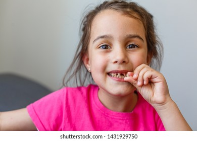closeup portrait of funny smiling little girl without one front tooth