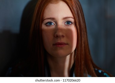 Closeup portrait of ginger woman with blue eyes partly in shadow.