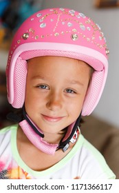 Close-up portrait of a girl of 8 years old, wearing a pink helmet decorated with rhinestones