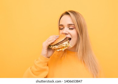 Closeup portrait of a girl biting a burger with her eyes closed on a yellow background, wearing orange clothing.Hungry girl eats a harmful food, holds in the hands of a great tasty burger.