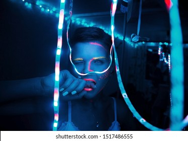 Close-up portrait of a girl in a blue room with neon and garlands winks bites her finger