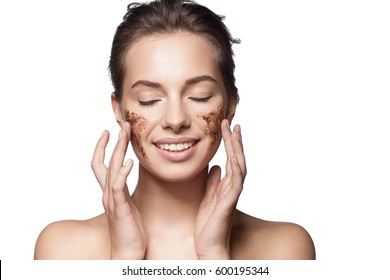 Close-up portrait of a girl with a brown scrub on her face doing peeling skin isolated on white background