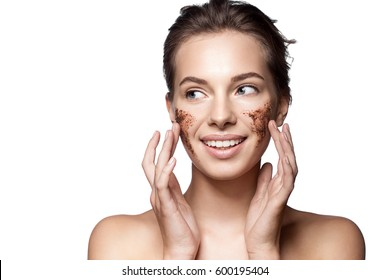 Close-up portrait of a girl with a coffee-scrub on her face making peeling skin isolated on white background