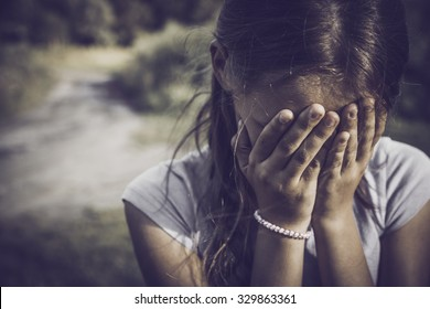 close-up portrait of a girl crying and covering her face