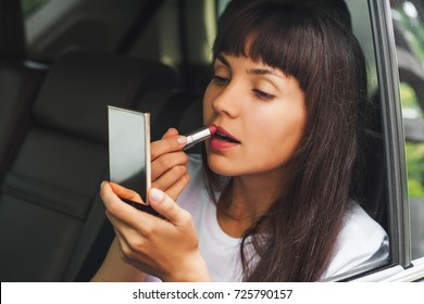 Close-up portrait of girl doing make-up, looking on herself at mirror and applying lipstick on her lips into a car.