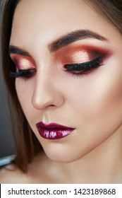Closeup portrait of a girl of fashion model in trendy make-up. Eye models with colorful glitter on the eyelids. The gaze of the girl is directed downwards