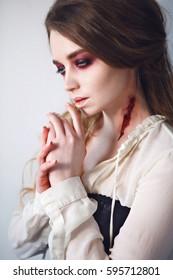 Close-up portrait of girl with fx make-up of vampire. Vampire bite.