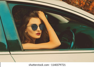 close-up portrait of a girl with glasses in the car in autumn time