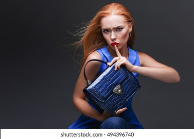 Closeup portrait of a girl holding a blue bag in his hands