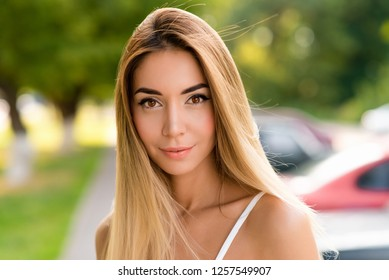 Closeup portrait, girl with long hair and tanned skin. Emotionally staring. Clean skin is a natural smile on the face. In the summer in nature. The concept of gentle beauty. A fresh look.