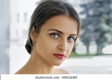 Close-up portrait of a girl with perfect clean skin against a light background