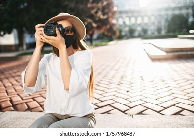 Close-up portrait of a girl photographer in hat with a protective medical mask on her face looks in the viewfinder and takes a photo