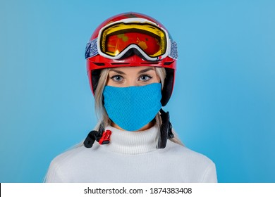 Close-up portrait of a girl skier wearing a light blu protective mask, helmet and glasses. A snowboarder on an light blu background. Covid19 coronavirus and the ski resort pandemic