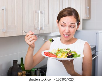 closeup portrait of glad young woman holding plate with green salad indoors