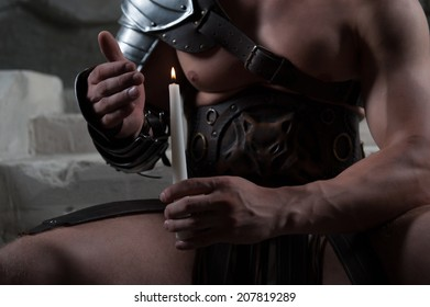 Closeup portrait of Gladiator in armour sitting on steps of ancient temple holding candle against dark background