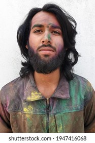 Closeup portrait of good looking young man covered with multi color holi powder and standing against white wall, Bearded and long haired Indian young guy celebrating Holi festival - Stock Photo