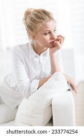 closeup portrait of a gorgeous blond young woman sitting in a white couch
