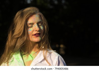 Closeup portrait of gorgeous blonde woman with long hair posing with paint Holi