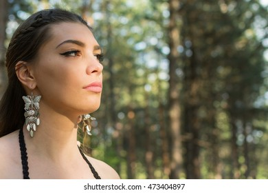 Closeup portrait of gorgeous boho young woman with earrings. Beautiful young woman in forest on sunny summer day, natural light, no retouch. Natural image look, no post-processing.