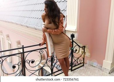 Close-up portrait of gorgeous brunette young woman wearing turquoise pajamas,autumn style, sitting next to the window. She's happy, smiling, touching her wavy hair.sensual woman on the balcony