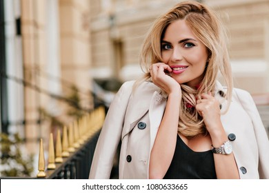 Close-up portrait of gorgeous european girl playfully posing in new beige coat. Outdoor photo of laughing blue-eyed female model having fun outside during walk.