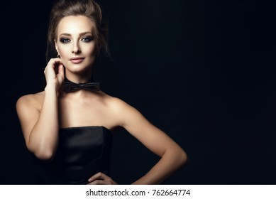 Closeup portrait of gorgeous glam woman with beautiful make up and updo hair wearing black corset dress and bow tie on her neck. Isolated on black background. Gamble and casino concept. Copy-space