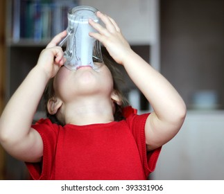 Close-up portrait of gorgeous little girl drinking a glass of milk at home, food and drink concept, healthy food, indoor